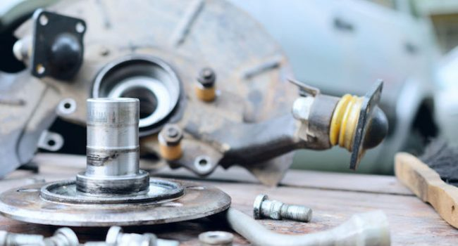 65609777 - old, oiled wheel hub lies on a wooden table. car repair in the field and at home.